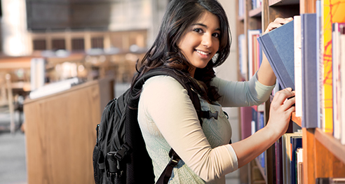 Student returning books on shelves in library